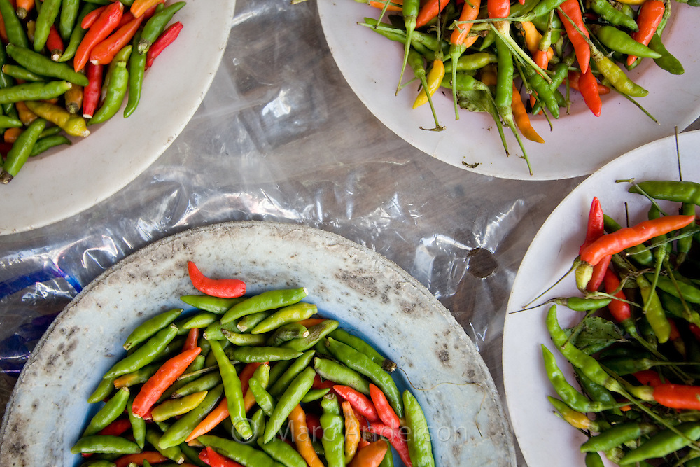 Plates of colourful green and red hot chillies in a market in Bangkok, Thailand