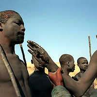 IPMG0366 South Africa, Flagstaff, 1998: Xhosa initiates are are forced by the `shepherd' to put mud into the mouth of a another initiate who refused to apply mud to his body with enough enthusiasm during their seclusion having undergone the circumcision rite of passage to manhood in tribal Xhosa culture in the former Transkei homeland, near Flagstaff, July 1998...Photograph by Greg Marinovich/South Photographs