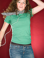 female teen (18 years old) with ear bud headphones, jumping and smiling