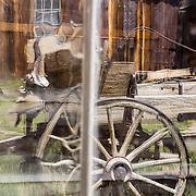"A window distorts a reflection of an old wagon at Bodie, California's official state gold rush ghost town. Bodie State Historic Park lies in the Bodie Hills east of the Sierra Nevada mountain range in Mono County, near Bridgeport, California, USA. After W. S. Bodey's original gold discovery in 1859, profitable gold ore discoveries in 1876 and 1878 transformed ""Bodie"" from an isolated mining camp to a Wild West boomtown. By 1879, Bodie had a population of 5000-7000 people with 2000 buildings. At its peak, 65 saloons lined Main Street, which was a mile long. Bodie declined rapidly 1912-1917 and the last mine closed in 1942. Bodie became a National Historic Landmark in 1961 and Bodie State Historic Park in 1962."