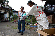 Mr Miura (52) from the NGO Heart Care Rescue, offering necessary supplies to Mr Mr Shinichi Sano (75) who often spends time in his house which he had to evacuate as Iitate village has high levels of radiation.