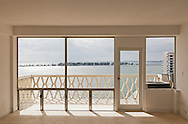 The interior living room and balcony with bay view of an unfurnished apartment in Miami, Florida WATERMARKS WILL NOT APPEAR ON PRINTS OR LICENSED IMAGES.