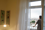 """A man looks at the view from one of the rooms's balconies at hotel """"Casa das Janelas com Vista"""" in Lisbon, Portugal"""