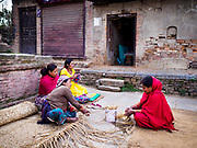 14 MARCH 2017 - BUNGAMATI, NEPAL: Women weave mat rugs in front of an earthquake damaged home in Bungamati. Recovery seems to have barely begun nearly two years after the earthquake of 25 April 2015 that devastated Nepal. In some villages in the Kathmandu valley workers are working by hand to remove ruble and dig out destroyed buildings. About 9,000 people were killed and another 22,000 injured by the earthquake. The epicenter of the earthquake was east of the Gorka district.            PHOTO BY JACK KURTZ