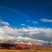 A rainbow stretches across the sky above the Vermilion Cliffs near Page, Arizona. The Vermilion Cliffs, which rise as much as 3,000 feet (914 meters), are the second step in the five-step Grand Staircase of the Colorado Plateau, which stretches from northern Arizona to southern Utah.  The cliffs are made up of sedimentary rocks, primarily sandstone, siltstone, limestone, and shale, that have eroded over millions of years. The Vermilion Cliffs were designated as the Vermilion Cliffs National Monumnet in 2000.