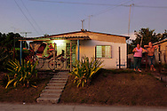 Family with horse carriage on their porch in the Campo Florido area of Ciudad de La Habana, Cuba.