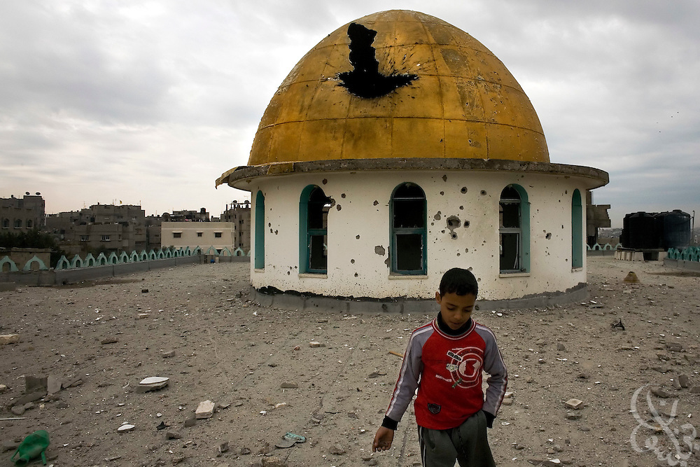 A Palestinian boy plays near a damaged mosque dome in the Jabal al-Ariyas district of Gaza City January 20, 2009. According to estimates by Palestinian authorities, 14% of the total structures in the Gaza Strip have been damaged during the recent 21 day Israeli military operation against HAMAS. The total cost of damage from the operation is estimated at between 1.5 to 1.9 billion dollars. ..