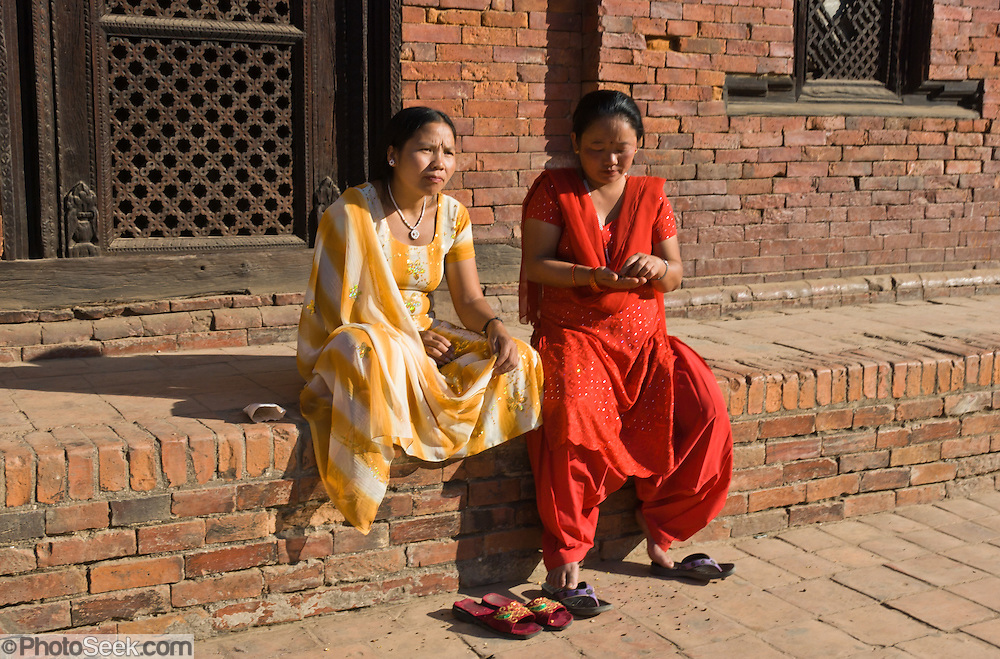 """Women in yellow and red saris, Patan, Nepal. Patan was probably founded by King Veer Deva in 299 AD from a much older settlement. Patan, officially called Lalitpur, the oldest city in the Kathmandu Valley, is separated from Kathmandu and Bhaktapur by rivers. Patan (population 190,000 in 2006) is the fourth largest city of Nepal, after Kathmandu, Biratnagar and Pokhara. The Newar people, the earliest known natives of the Kathmandu Valley, call Patan by the name """"Yala""""  (from King Yalamber) in their Nepal Bhasa language. UNESCO honored Patan's Durbar Square (Palace Square) as one of the seven monument zones of Kathmandu Valley on their World Heritage List in 1979. All sites are protected under Nepal's Monuments Preservation Act of 1956."""