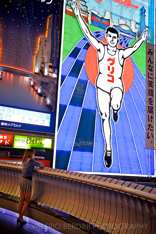 A girl lean from ebisu-bashi bridge in front of the landmark neon of the running man. One of the three best known spots of Osaka, this is an adv of Glico candy confectionery. It has been here since 1935. Osaka, Japan 2013