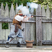 "A costumed historical interpreter fires a 1600s matchlock musket at Jamestown Settlement, Virginia, USA. Jamestown Settlement, operated by the state's Jamestown-Yorktown Foundation, chronicles 1600s Virginia and the convergence of Powhatan Indian, European, and west central African cultures. Created as part of the 350th anniversary celebration in 1957 as ""Jamestown Festival Park,"" Jamestown Settlement is adjacent to the complementary ""Historic Jamestowne"" museum (which is on Jamestown Island, is the actual historic and archaeological site where the first settlers lived, and is run by the National Park Service and Preservation Virginia)."