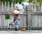"""A costumed historical interpreter fires a 1600s matchlock musket at Jamestown Settlement, Virginia, USA. Jamestown Settlement, operated by the state's Jamestown-Yorktown Foundation, chronicles 1600s Virginia and the convergence of Powhatan Indian, European, and west central African cultures. Created as part of the 350th anniversary celebration in 1957 as """"Jamestown Festival Park,"""" Jamestown Settlement is adjacent to the complementary """"Historic Jamestowne"""" museum (which is on Jamestown Island, is the actual historic and archaeological site where the first settlers lived, and is run by the National Park Service and Preservation Virginia)."""