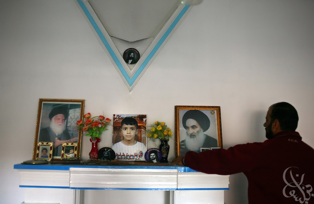 Sattar Hashim, an Iraqi federal protection service guard keeps a small memorial to his murdered 12 year old son, Hassan (seen in center photo) at his home in the Na'ariya district of Baghdad, Iraq November 17, 2006.   Hassan and 33 other children were killed when a suicide bomb detonated in their neighborhood on July 13, 2005.
