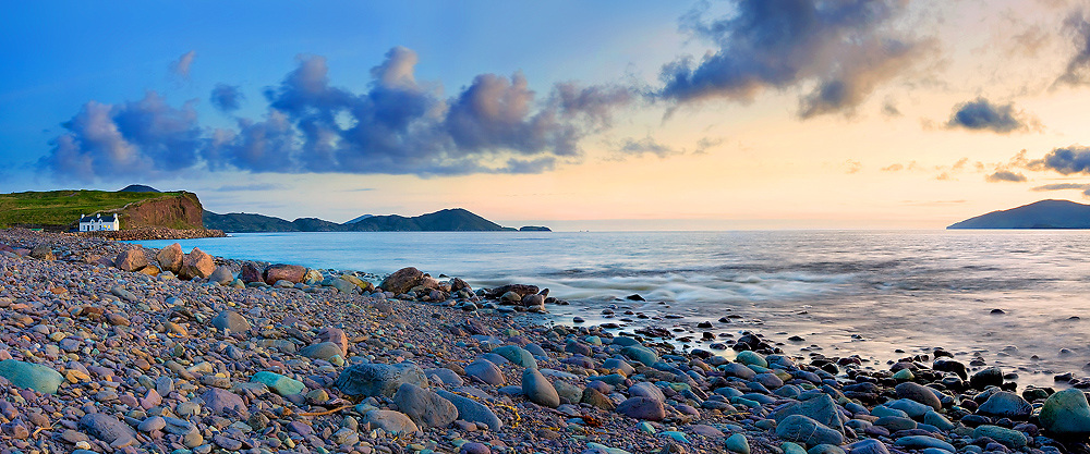 Waterville is a town in County Kerry, Ireland on the Iverah Peninsula. The town is sited on a narrow isthmus, with lough Currane on the est side and Ballinskelligs Bay on the west. View on Cottage and Skellig Bay Golfcourse during sunset. / wv033