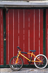 design yellow bicycle rest against red garage doors.