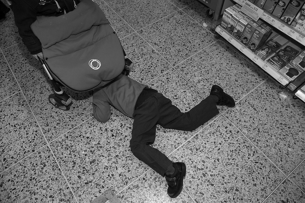 Ben plays hide and seek under his brother's pram at the chemist in Berkhamsted Wednesday, March 25, 2015.  It was in Kenya, on an assignment photographing Masaai mothers and children, where I was reminded of the power of the familiar and the mundane.&nbsp;Amid the rugged landscapes and the cattle-herding families whose lives still revolve around ancient rhythms, I began to wonder about my own attitudes. Why did I think mothers in this different and exotic environment were worthy of being documented? Why did I think motherhood in my own world lacked that luster? Why is the remote more valuable to a photographer than the world right around them? &nbsp;And I realized I had turned a blind eye to the profound, complex story right next to me: in the school runs, the trips to the store, the swimming lessons and the countless birthday parties and field trips.&nbsp;<br /> It is the world I navigate every day with my two young sons.&nbsp;This project has let me see photographs where before I thought there were none. It has allowed me to see the universality of my life and how it is reflected in so many other lives. (Elizabeth Dalziel) #thesecretlifeofmothers #bringinguptheboys #dailylife