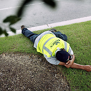 A landscaping worker asleep on the grass in Wilmington, NC.
