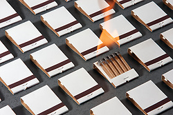Rows of white generic match books, one of which is on fire--easily customizable matchbook covers