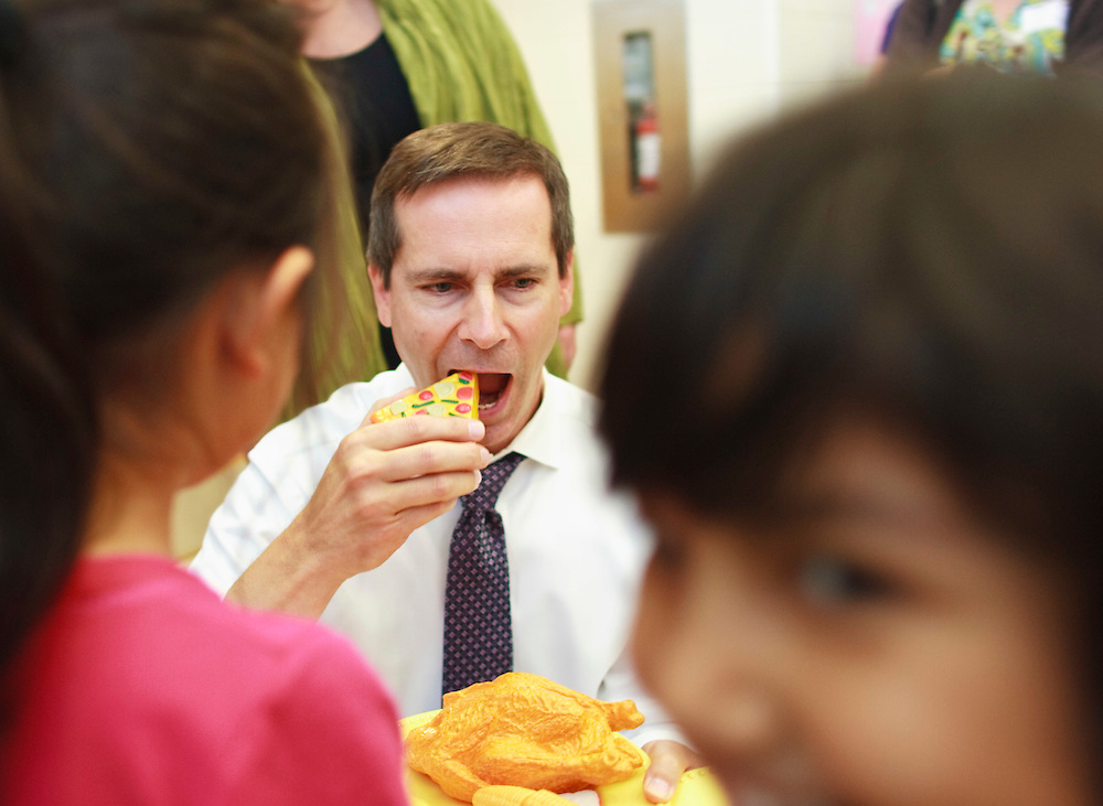 London, Ontario ---10-10-08---  Premier Dalton McGuinty takes a bite out of a piece of toy thanksgiving dinner presented to him by Amaris Peng, left, and Eshal Ali during a visit Stoney Creek Public School in London, Ontario, October 8, 2010.<br /> GEOFF ROBINS The Globe and Mail