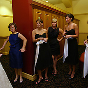 A bride shows off her dress and asks for final thoughts from her bridesmaids and friends as they ceremony nears.