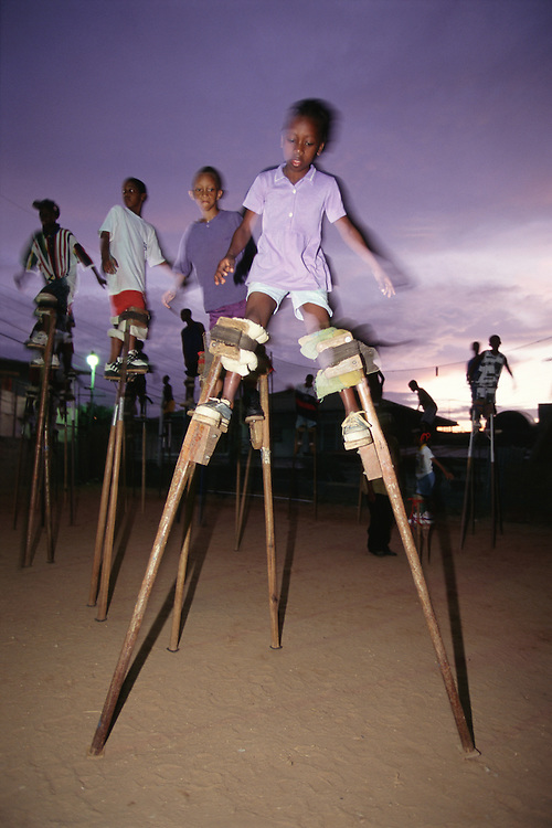 """Trinidad and Tobago """"MOKO JUMBIES: The Dancing Spirits of Trinidad"""".A photo essay about a stilt walking school in Cocorite, Trinidad..Dragon Glen de Souza founded the Keylemanjahro School of Art & Culture in 1986. The main purpose of the school is to keep children off the streets and away from drugs..He first taught dances like the Calypso, African dance and the jig with his former partner Cathy Ann Samuel.  Searching for other activities to engage the children in, he rediscovered the art of stilt-walking, a tradition known in West Africa as the Moko Jumbies , protectors of the villages and participants in religious ceremonies. The art was brought to Trinidad by the slave trade and soon forgotten..Today Dragon's school has over 100 members from age 4 and up..His 2 year old son Mutawakkil is probably the youngest Moko Jumbie ever. The stilts are made by Dragon and his students and can be as high as 12-15 feet. The children show their artistic talents mostly at the annual Carnival, which today is unthinkable without the presence of the Moko Jumbies. A band can have up to 80 children on stilts and they have won many of the prestigious prizes and trophies that are awarded by the National Carnival Commission. Designers like  Peter Minshall , Brian Mac Farlane and Laura Anderson Barbata create dazzling costumes for the school which are admired by thousands of  spectators. Besides stilt-walking the children learn the limbo dance, drumming, fire blowing and how to ride  unicycles..The school is situated in Cocorite, a suburb of Port of Spain, the capital of Trinidad and Tobago..all images © Stefan Falke"""