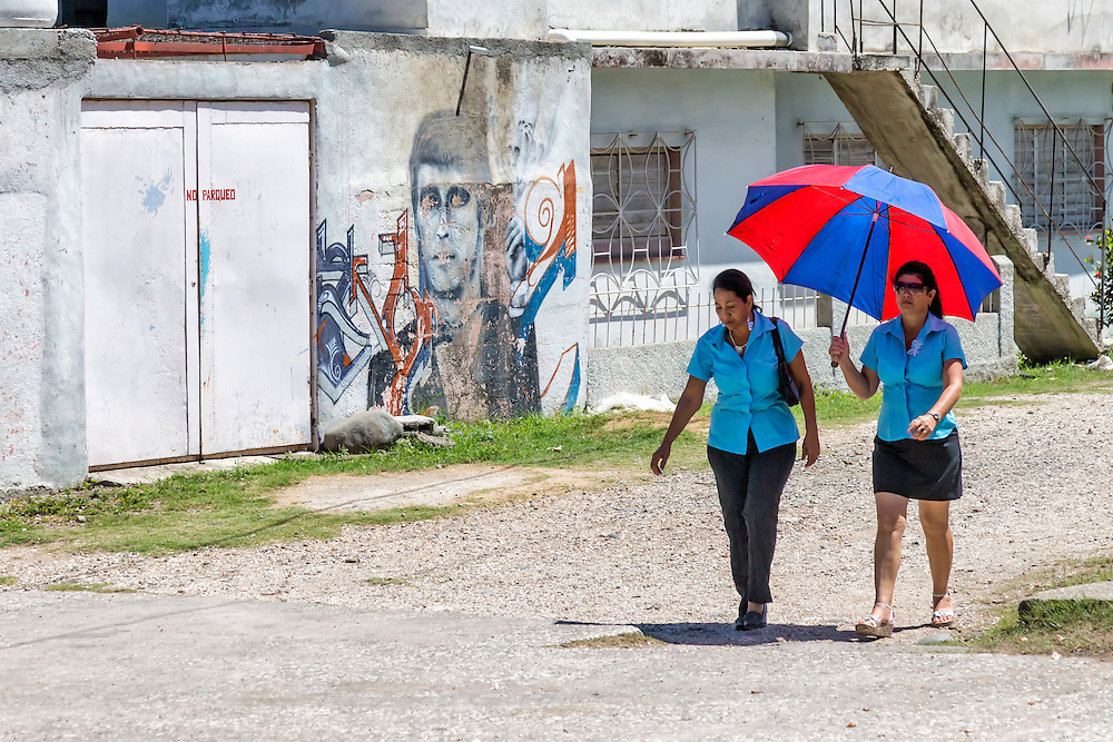 Women walking with an umbrella on a hot day in Bayamo, Granma, Cuba.