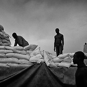 Cameroon/CAR refugees/ Volonteers carry bags of corn on a truck destinated to a food distribution, on october 21, 2014, in the site of Mbile, east of Cameroon. /UNHCR/O.Laban-Mattei/October 2014