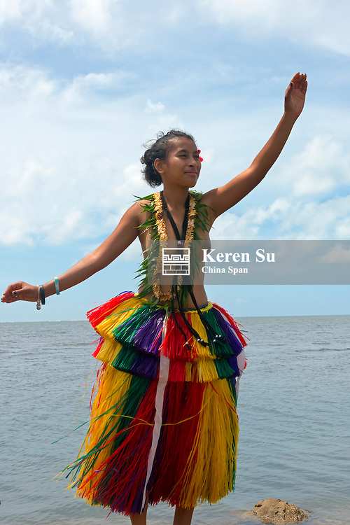 Yapese girl in grass skirt dancing by the ocean, Yap Island, Federated States of Micronesia