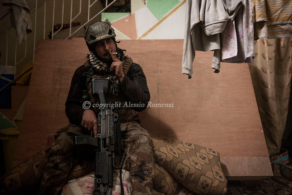 Iraq, Mosul: A Golden Division member takes a rest during a house by house advance in west Mosul. Alessio Romenzi