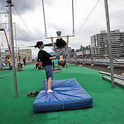Student Ashleigh Blair practices a knee hang on a low bar at Trapeze School New York during the June 4th morning class. The two hour beginner session taught the nine students in attendance the basics of flying trapeze -- including knee hangs and backwards somersaults -- in their facility on the roof of Pier 40...CREDIT: Daniella Zalcman for The Wall Street Journal.SLUG: NYMETROMONEY_Trapeze