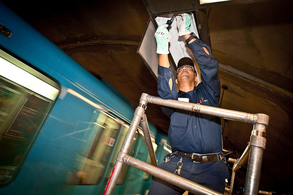 L'électricien Mouhadi Ahmed  répare des circuits de néon sur le quai de la station Monk.
