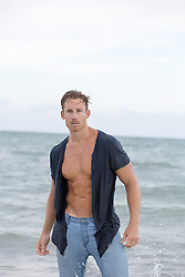 man in a ripped shirt in the ocean