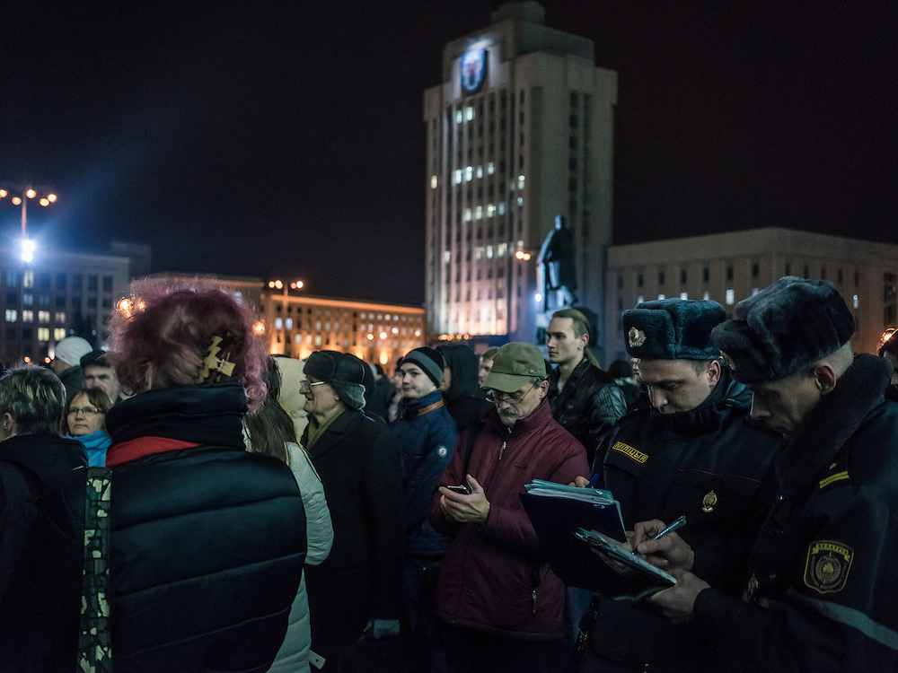 Police at right fill out legal forms to fine Mikalai Statkevich, a former opposition presidential candidate and political dissident, for organizing an illegal rally to commemorate the nineteenth anniversary of a referendum which enshrined authoritarian changes in Belarus's constitution on Tuesday, November 24, 2015 in Minsk, Belarus.