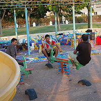 Migrants from Algeria and Morocco sit and talk in a children's play area where they sleep in Patras, Greece