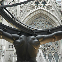 Rear of statue of Atlas supporting the world, with facade of St. Patrick's cathedral across 5th Ave.