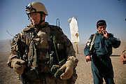 An afghan police man stands a little mistrustful a german pioneer platoon off OP North to check culverts around to make sure safety bars are still fixed to avoid IED planting beneath the street.