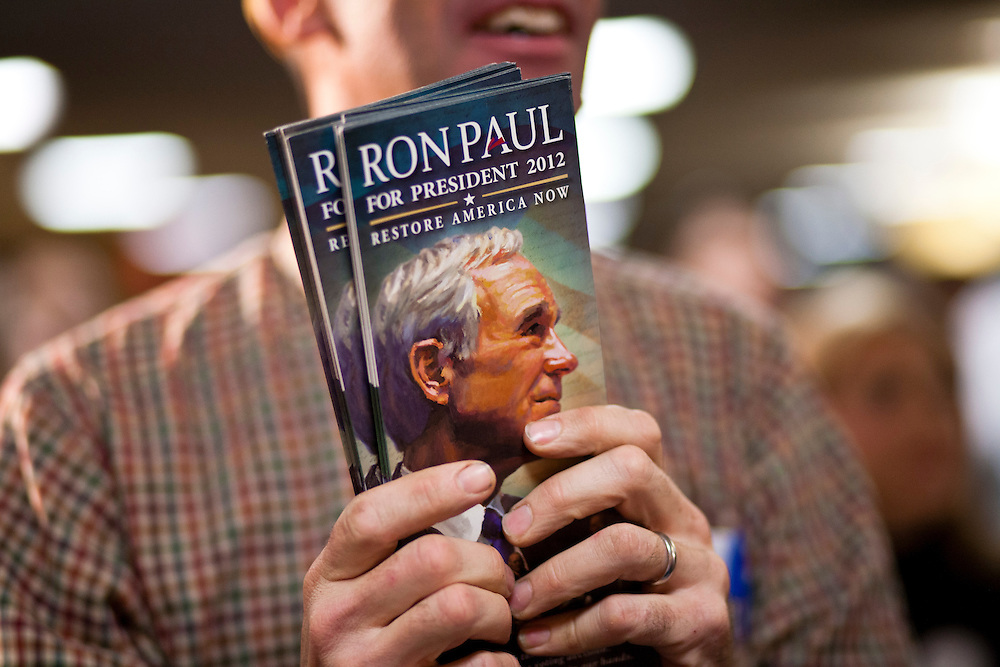 A man holds brochures for Republican presidential candidate Ron Paul before a campaign rally at the SteepleGate Inn on Monday, January 2, 2012 in Davenport, IA.