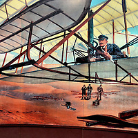 Orville Wright Painting of First Flight at Kill Devil Hills, North Carolina<br /> Two brothers who did not finish high-school and ran a marginally successful newspaper and then a bicycle shop shared a dream: to create a control that would master motor-driven flight. From 1899 until 1903, the Wright Brothers generated extensive data from a home-built wind tunnel. The duo also tinkered with bike parts and motors to create and test various gliders. This painting at the Wright Brothers National Memorial depicts their first manned flight of 120 feet at Kill Devil Hill on December 17, 1903.