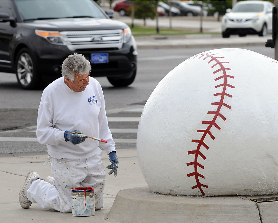 jt033117j/a sec/jim thompson/   Max Jaramillo of Jaramillo Painting touches up the red seams of the giant baseball infant of Isotopes Park Friday afternoon. The ball was first located at Tingley Fields from 1937-68 and was moved to the corner of University and Stadium in 1969 when the original Albuquerque Sports Stadium was built. Friday March 31, 2017. (Jim Thompson/Albuquerque Journal)