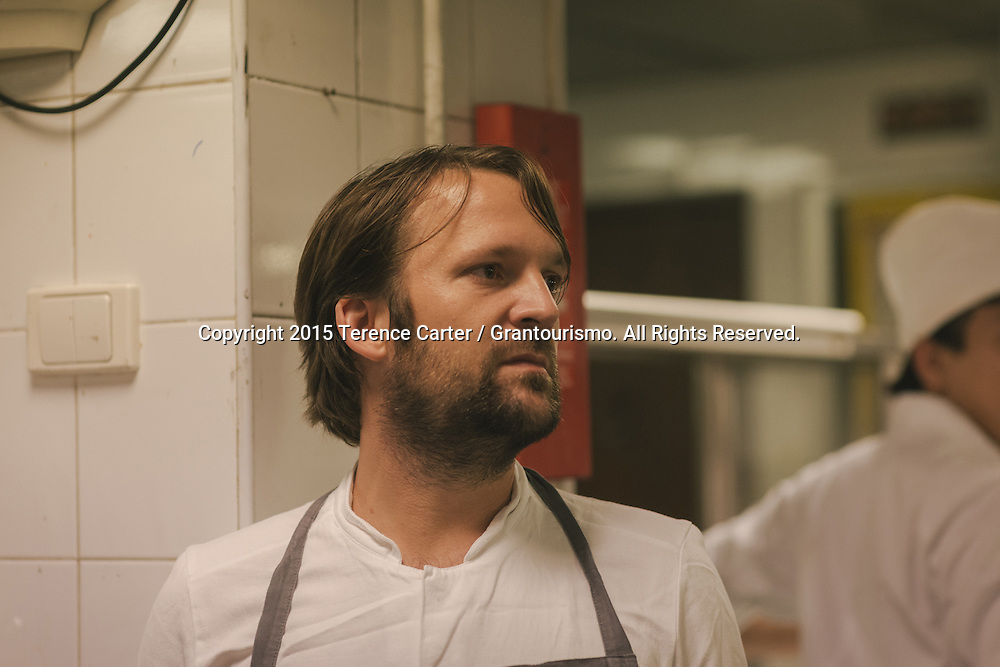 Due to his late arrival in Bangkok because of a family emergency back in Copenhagen, Chef Redzepi looks on nervously as final preparations for the dinner are made by the chef. Copyright 2015 Terence Carter / Grantourismo. All Rights Reserved.