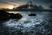 A deep swell forcing through a narrow channel causes upwelling / upsurge of sea water at this headland at sunset at Rhoscolyn, North Anglesey