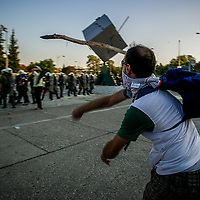 A man throws a javelin style stick at riot police during a demonstration where 17,000 cab drivers, students, and futbol fans marched in the northern port of Thessaloniki, Greece Sept 10, 2011. Marchers were protesting against austerity measures just before Prime Minister George Papandreou spoke.  Police were fired on by flare guns sticks and stones and even gas bombs, according to police representatives.  Photo Ken Cedeno