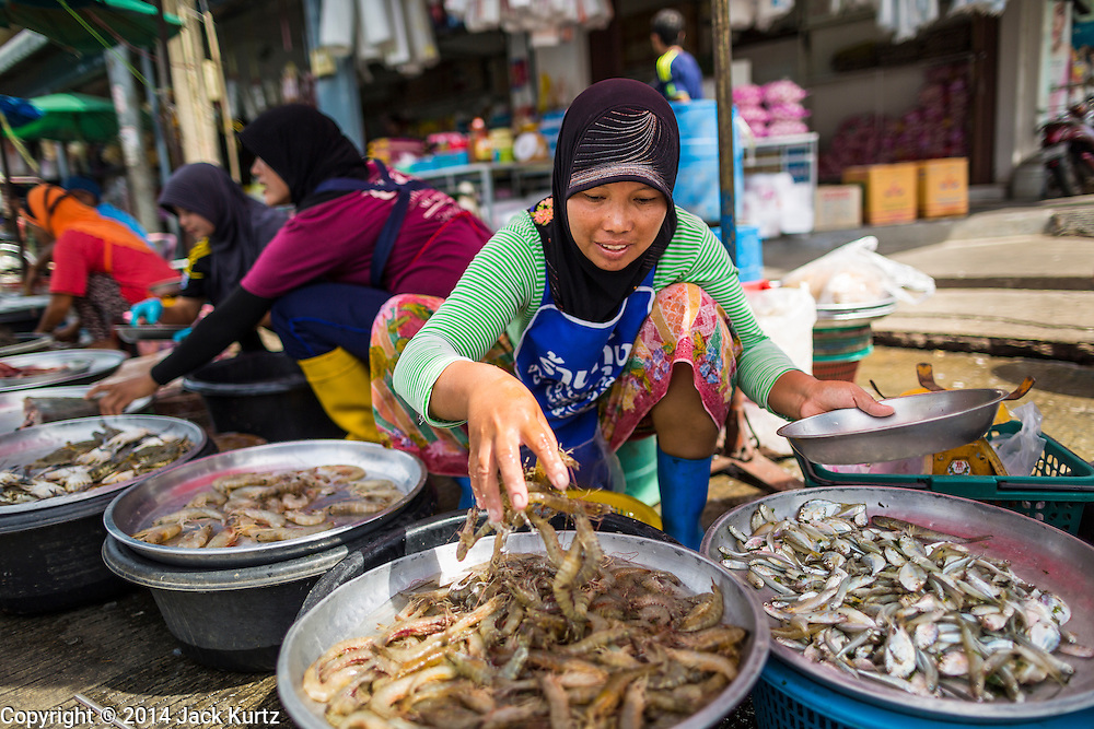 29 JULY 2014 - HAT YAI, SONGKHLA, THAILAND: Muslim women sell shrimp and seafood in the market in Hat Yai. Hat Yai is the 4th largest city in Thailand and the largest outside of the Bangkok metropolitan area. It's less the 50 miles from the Malaysian border and is a popular vacation spot for Malaysian and Singaporean tourists.       PHOTO BY JACK KURTZ
