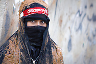 A shi'a muslim girl, wearing a black veil, covered in mud, during the Day of Ashura, on which shi'a muslims commemorate the martyrdom of Husayn ibn Ali, grandson of Muhammad, and third Shi'a imam (Bijar, Iran, 2012).<br />