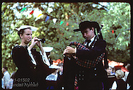 Man & woman in traditional Breton costumes play bagpipe, recorder @ pardon festival;town of Crac'h France