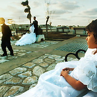 A flower girl waits to have her picture taken by a wedding photographer along the Malecón in Havana.