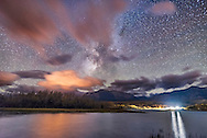 The summer Milky Way and galactic centre area over Maskinonge Pond at Waterton Lakes National Park, September 23, 2016, amid a constant stream of clouds coming over the mountains and Continental Divide this night. <br /> <br /> The clouds are lit by sodium vapour lights from Waterton townsite, while the bright lights at right are from the white LED streetlamps at the Park Entrance Gate, mostly shielded but still overly bright. <br /> <br /> This is a stack of 4 x 30 second exposures for the ground, mean combined to smooth noise, and one 30 second exposure for the sky, all at f/2.2 with the 20mm Sigma lens and at ISO 3200 with the Nikon D750 on a moonless night.