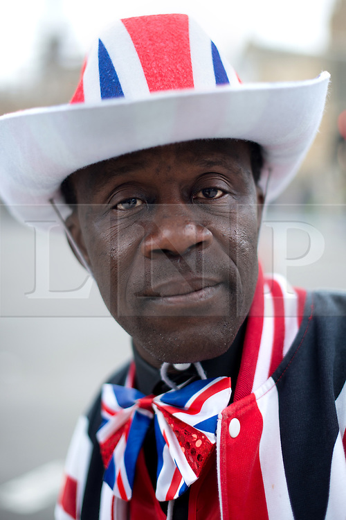 © Licensed to London News Pictures. 17/04/2013. London, UK. A member of public dressed in Union Jack waits for the funeral of former British Prime Minister Baroness Thatcher at Trafalgar square on April 17, 2013 in London, England.Photo credit : Peter Kollanyi/LNP