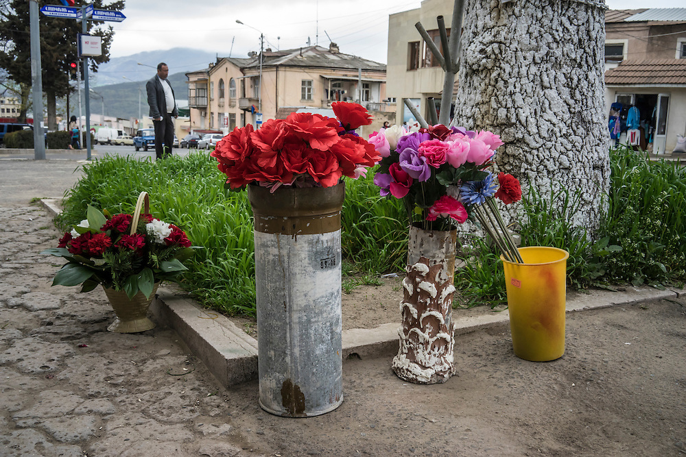 STEPANAKERT, NAGORNO-KARABAKH - APRIL 22: Plastic flowers are sold in an artillery casing outside a shop on April 22, 2015 in Stepanakert, Nagorno-Karabakh. Since signing a ceasefire in a war with Azerbaijan in 1994, Nagorno-Karabakh, officially part of Azerbaijan, has functioned as a self-declared independent republic and de facto part of Armenia, with hostilities along the line of contact between Nagorno-Karabakh and Azerbaijan occasionally flaring up and causing casualties. (Photo by Brendan Hoffman/Getty Images) *** Local Caption ***