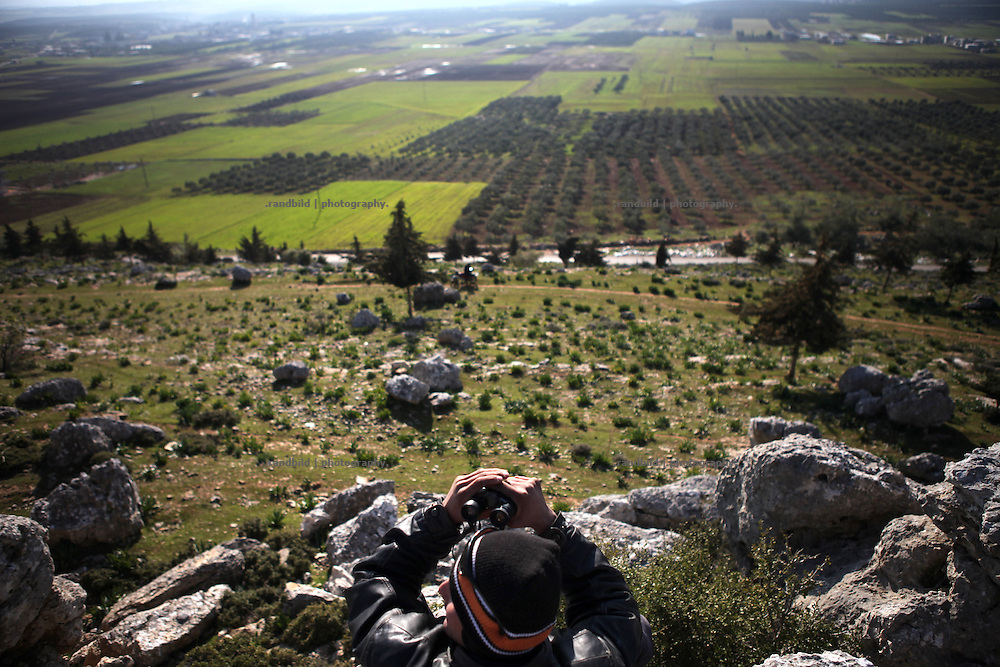 A member of the syrian opposition observes a green and fecund plain to look out for syrian troops near Al Kastan, Province of Idlib, Syria.