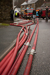 © Licensed to London News Pictures. 22/12/2012. Helston, UK. Pumping equipment being used by Cornwall Fire and Rescue Service to pump flood water away from St Johns Road. The River Cober burst its banks over night after heavy rain across the South West. The Environment Agency issued a Severe flood warning for the River Cober. Photo credit : Ashley Hugo/LNP